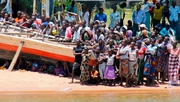 People watch from the banks of Lake Victoria as Tanzanian rescue workers continue to search for victims