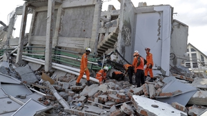 Rescuers search for survivors at the collapsed Roa Roa hotel building in Palu
