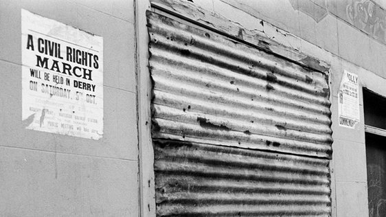 A boarded-up premises in Derry city on 7 May 1969. A notice publicising a civil rights march is visible. (C) RTÉ Archives 2142/022