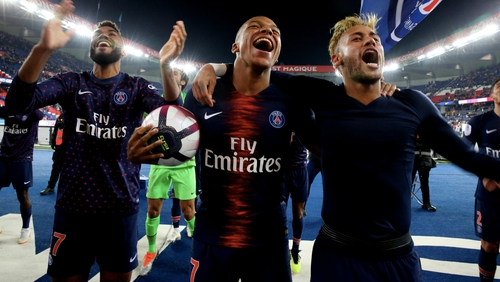 Kylian Mbappe celebrates with the match ball and Neymar after the historic victory