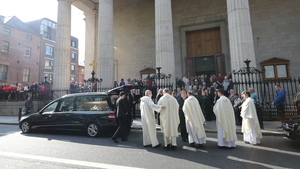 The coffin of Emma Mhic Mhathúna is carried from St Mary's Pro-Cathedral following her funeral mass