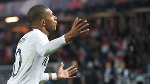 Kylian Mbappe celebrates after scoring a late penalty
