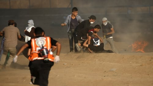 Palestinians medics help a protester near the border