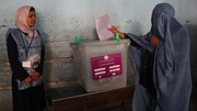 A woman casts her vote at a polling station during the parliamentary elections in Herat