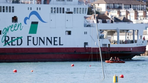 The mast of a sunken yacht is seen close to the Red Funnel ferry
