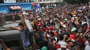 Members of the migrant caravan push forward at a gate separating Guatemala from Mexico in Ciudad Tecun Uman, Guatemala