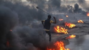 A protester fires stones with a slingshot during clashes near the border between Israel and Gaza