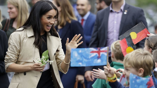 The Duchess of Sussex waves at children during a visit to Albert Park Primary School in Melbourne (PA)