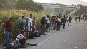 Migrants travelling towards the United States taking a rest along a road, hoping to hitch a ride on a passing vehicle