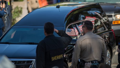 Officers salute as the hearse carrying the body of Sgt Ron Helus passes by