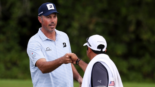 Kuchar and his caddie bump fists on the green in Mexico