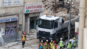 Rescue workers at the site where two dilapidated apartment buildings collapsed in Marseille