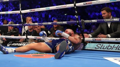 Eddie Hearn checks on Tony Bellew of England after he is knocked out by Oleksandr Usyk