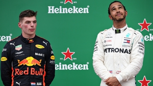 Lewis Hamilton celebrates on the podium alongside second-placed Max Verstappen
