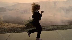 A woman runs as firefighters work to control a flare up due to flying embers from the Woolsey Fire in Calabasas