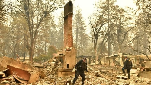 Emergency service personnel search for human remains at a burned residence in Paradise, California