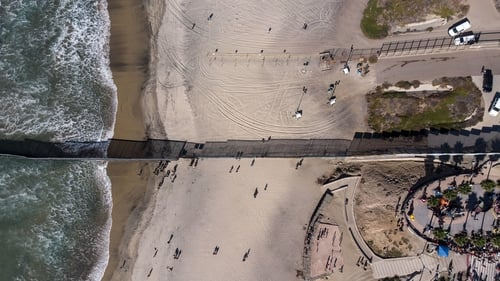 Groups of migrants have been gathering on the beach at the border fence that separates Mexico from California