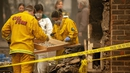 Rescue workers sift debris for human remains at a burned residence in Paradise