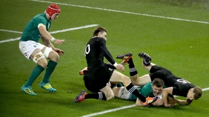 Jacob Stockdale crosses the try line against New Zealand despite the efforts of Damian McKenzie and Beauden Barrett