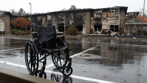 A wheelchair sits in front of a senior living facility that was destroyed by fire in Paradise, California