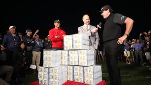 Phil Mickelson celebrates with the winnings after defeating Tiger Woods in The Match