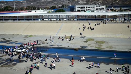 Migrants cross the dry riverbed of the Tijuana River trying to get to the El Chaparral port of entry