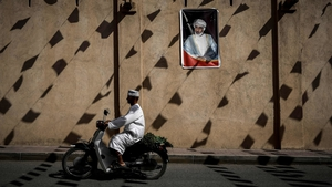 A man rides a motorcycle past a wall bearing a portrait of Oman's Sultan Qaboos. Photo: Philippe Lopez/AFP/Getty Images