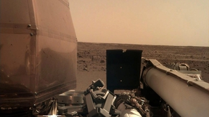 The image shows part of the spacecraft and the Martian surface in the distance