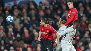 Manchester United defender Chris Smalling leaps above Kevin Mbabu of Young Boys at Old Trafford