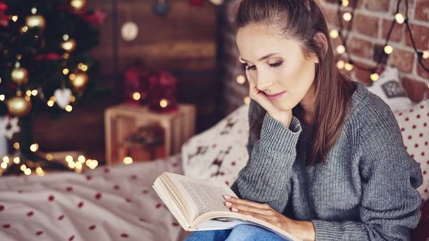 Woman reading a book in bedroom at christmas