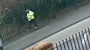 Security camera material shows a man in a high-visibility coat walking near a school