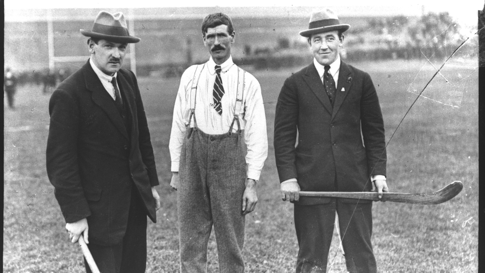 Image - Michael Collins, Mr Dunphy and Harry Boland, at a GAA hurling match at Croke Park, Dublin 1921. Michael Collins and Harry Boland are both holding hurleys. Photo: RTE Photographic Archive