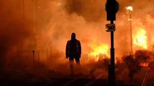 A protester stands near a fire in Bordeaux, southwestern France | Image: Nicolas Tucat/AFP/Getty