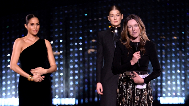 Clare Waight Keller is watched by Meghan and Rosamund Pike as she speaks on stage after receiving the award for British Designer of the Year Womenswear Award