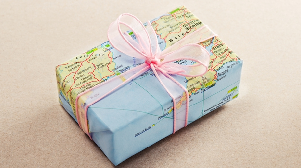 A bon voyage gift wrapped with map paper and pink bow