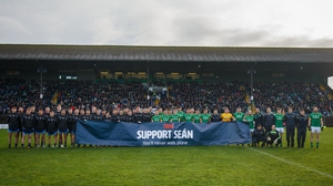 The two teams display a banner in support of Sean Cox before the game