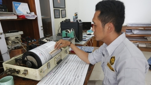 An officer examines a seismograph at the Anak Krakatau volcano monitoring station in Indonesia