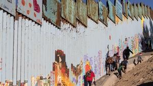 Migrants from Honduras try to walk along the US-Mexico border fence in Playas de Tijuana, Baja California State, Mexico