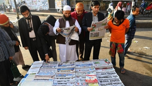 Bangladeshi people read newspapers carrying headlines on the general election results