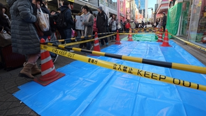 Pedestrians walk past the roped-off crime scene in Tokyo this morning