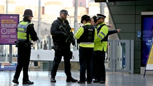 Armed police officers stand guard at Manchester's Victoria Metrolink station today