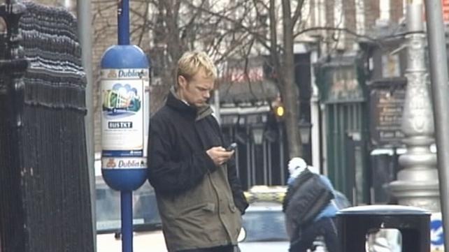 Man sending text message on mobile phone, Dublin (2004)