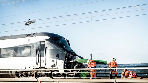 Men work at the accident site next to a passenger train standing on the rails in Nyberg, Denmark