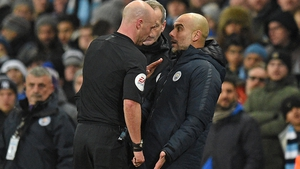 Referee Anthony Taylor (L) has words with Pep Guardiola (R)
