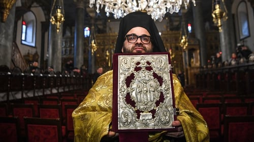 An Orthodox cleric holds the Bible before the start of a ceremony for the signing of the 'Tomos' decree