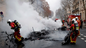 Firefighters extinguish vehicles on fire near the Seine river as clashes erupt in Paris