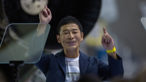 Yusaka Maezawa holds a ticket for Elon Musk's SpaceX rocket trip around the moon
