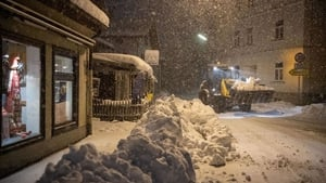 A wheel loader transports snow to clear the streets in Miesbach, southern Germany, during heavy snowfall