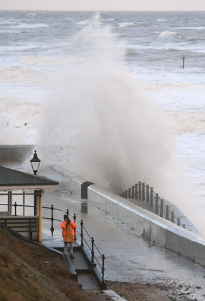 Waves crash against the sea wall at Cromer in Norfolk