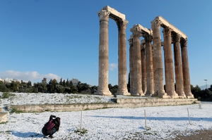 A young girl takes pictures of the snowy Temple of Olympian Zeus in central Athens, Greece